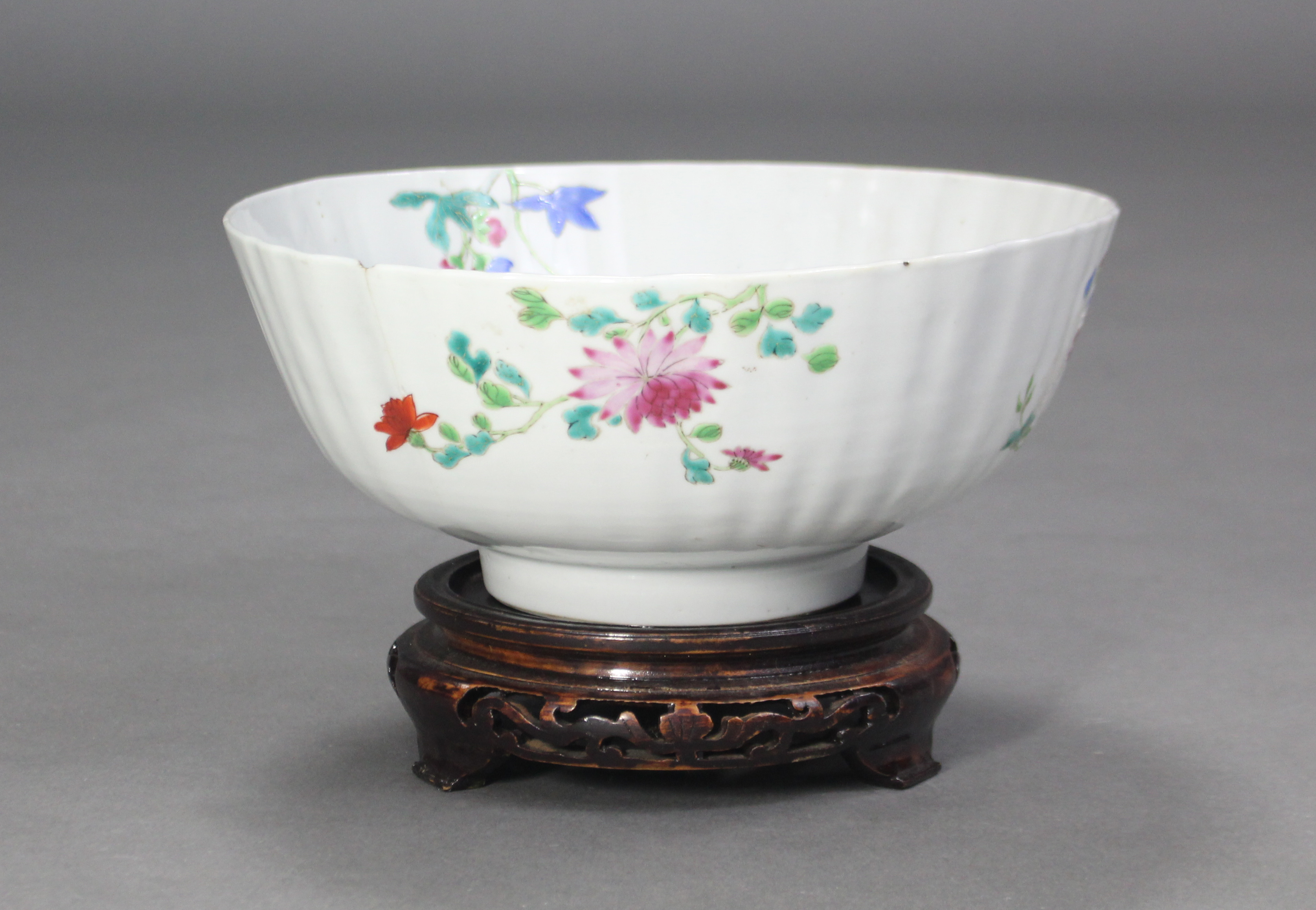 Lot 219 - An 18th century Chinese famille rose fluted punch bowl, painted with a formal flower garden & rock-
