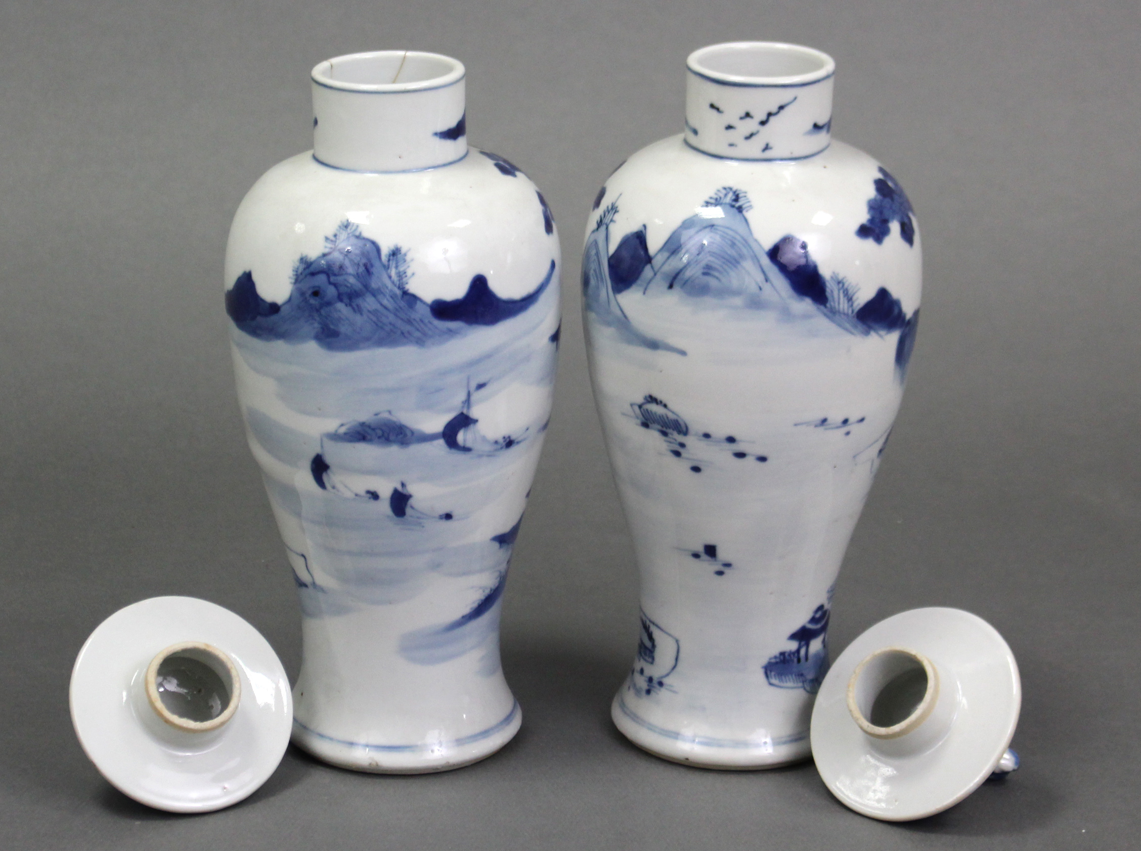 Lot 199 - A pair of Chinese blue & white porcelain slender baluster vases & covers, each with river