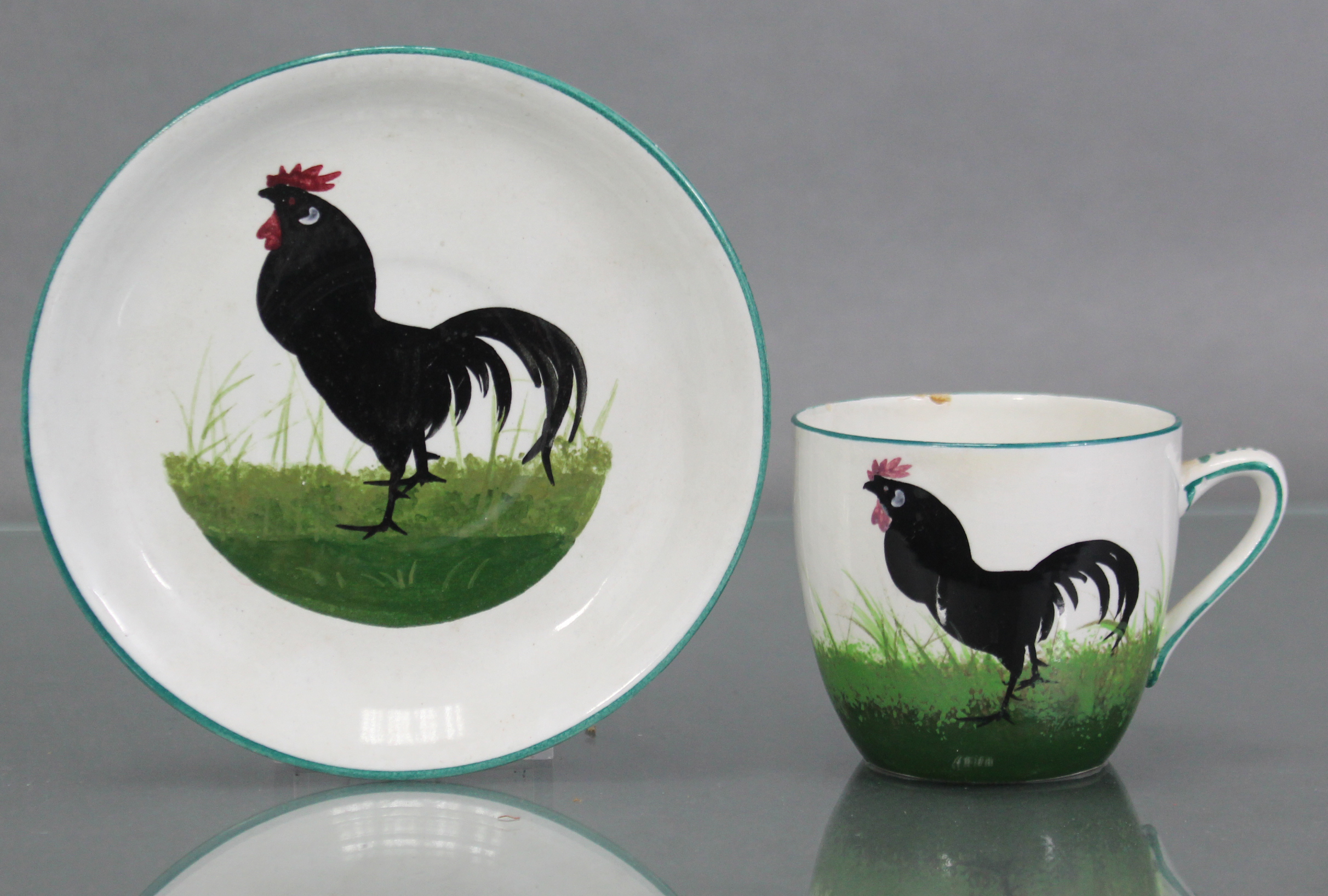 Lot 164 - A Wemyss pottery cream-ground teacup & saucer with painted decoration of a cockerel amongst grass;