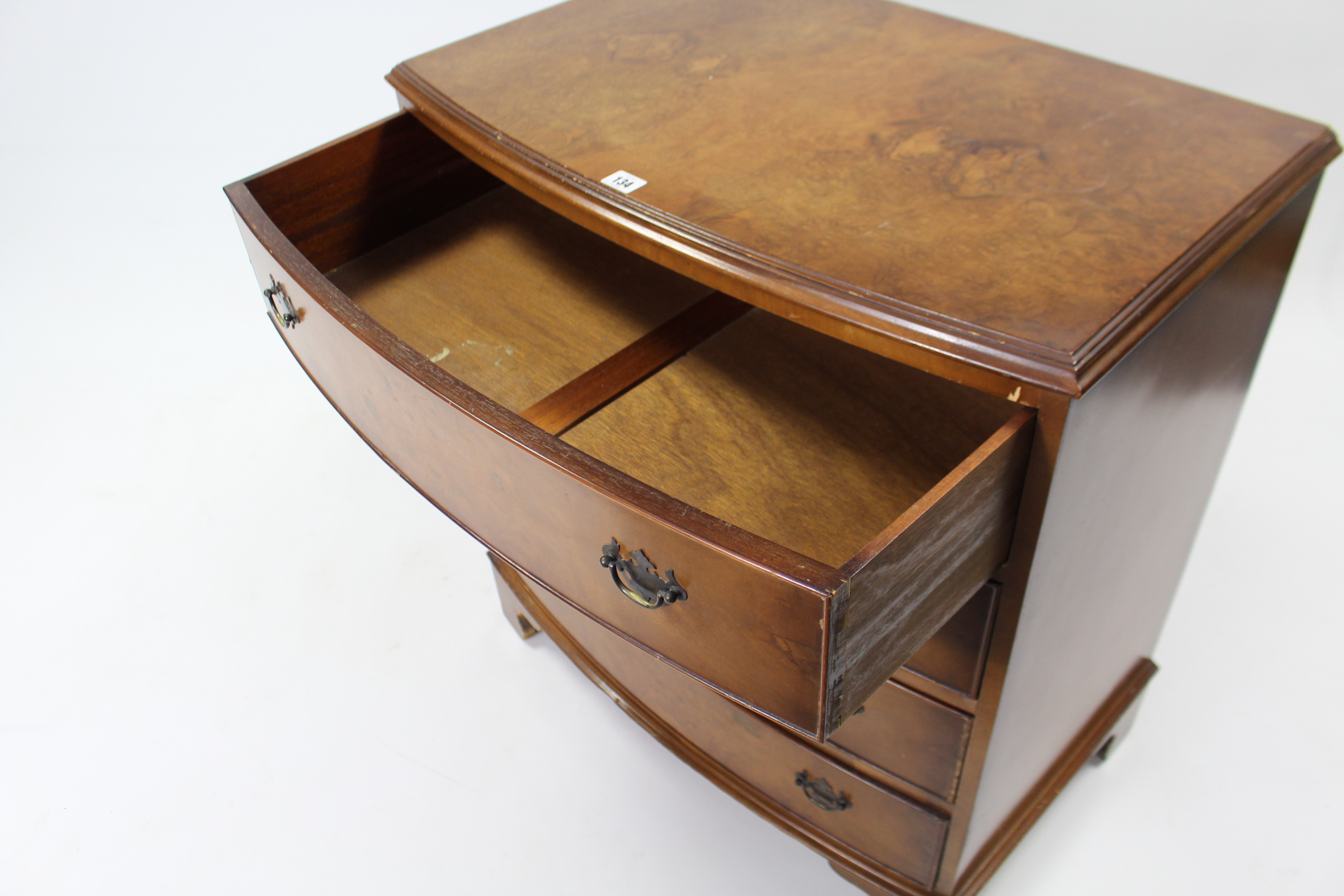 Lot 134 - A reproduction walnut bow-front chest, fitted four long drawers with brass swing handles, & on
