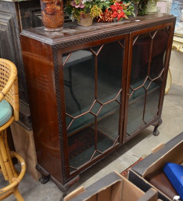 Lot 50 - A mahogany bookcase with blind fret cut banding around two astragal glazed doors, raised on short