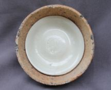 A Song dynasty Qingbai porcelain dish, with a light green glaze fused to the kiln saggar,