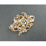An 18ct yellow and white gold brooch set with nine round brilliant cut diamonds each approximately