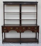 An 18th century South Wales oak dresser, the rack with a moulded cornice above two open shelves,