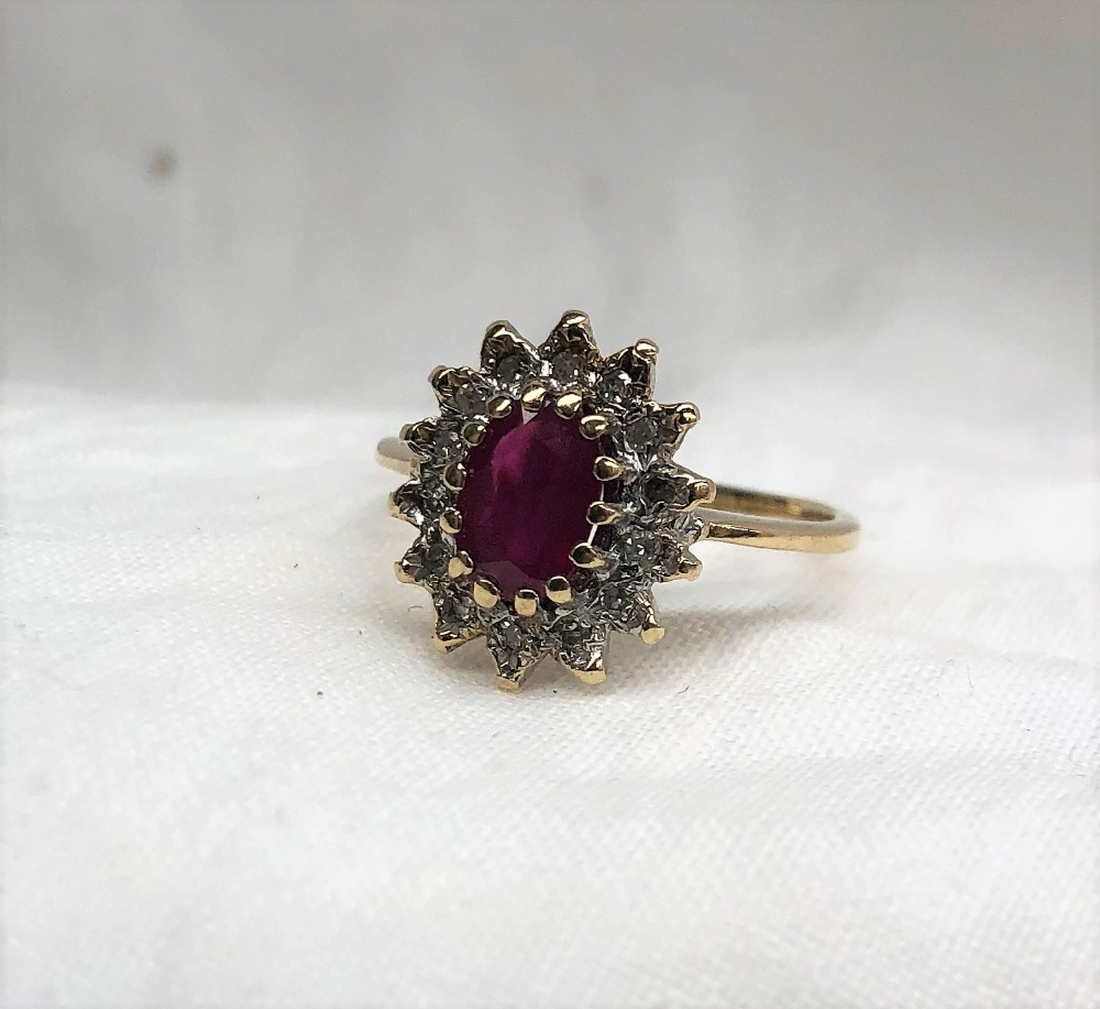 Lot 35 - A ruby and diamond cluster ring the central oval faceted ruby surrounded by fourteen diamonds to a
