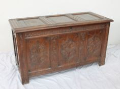 A 17th century oak coffer, the split pin hinged top with three panels,