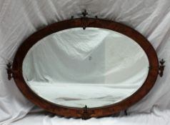 A 20th century copper framed wall mirror of oval form, with flaming vase mouldings,