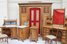 An Arts and Crafts light oak bedroom suite, comprising a triple wardrobe, wash stand,
