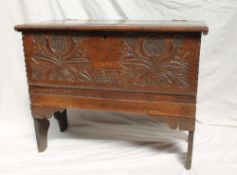 An 18th century oak coffer, the planked top above a leaf and flower carved front on slab ends, 87.