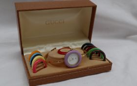 A Lady's Gucci wristwatch with a white dial and interchangeable bezels,