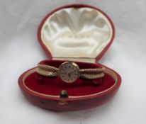 A Lady's 9ct yellow gold Omega wristwatch, the gilt dial with batons on an integral strap,