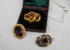 A Victorian brooch, set with a central faceted amethyst in a yellow metal mount,