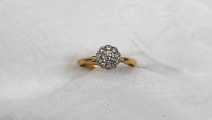 A diamond cluster ring, with a central round brilliant cut diamond approximately 0.