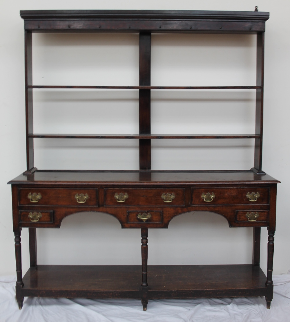 An 18th century South Wales oak dresser, the rack with a moulded cornice...