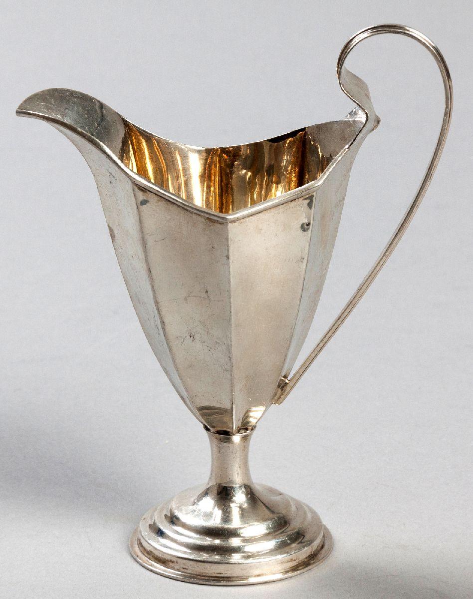 Lot 22 - AN EDWARDIAN SILVER CREAMER, BIRMINGHAM 1904, W & A, C-scroll reeded handle, segmented body on a