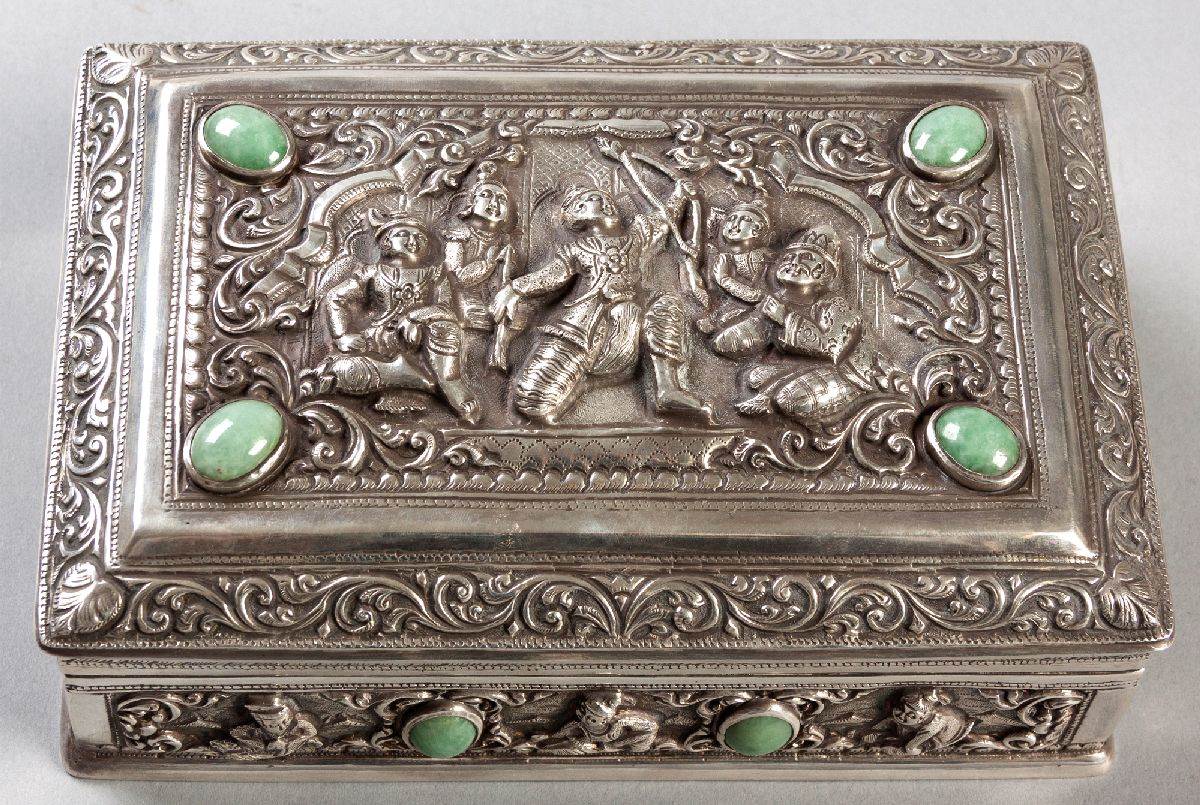 Lot 29 - A THAI SILVER CASKET, the hinged top embossed with a court scene, scrolls and swags, inset with jade