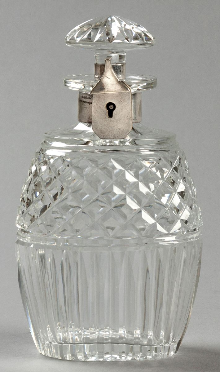 Lot 52 - A GLASS AND SILVERPLATE TANTALUS DECANTER, the removable stopper fitted with locking mechanism,