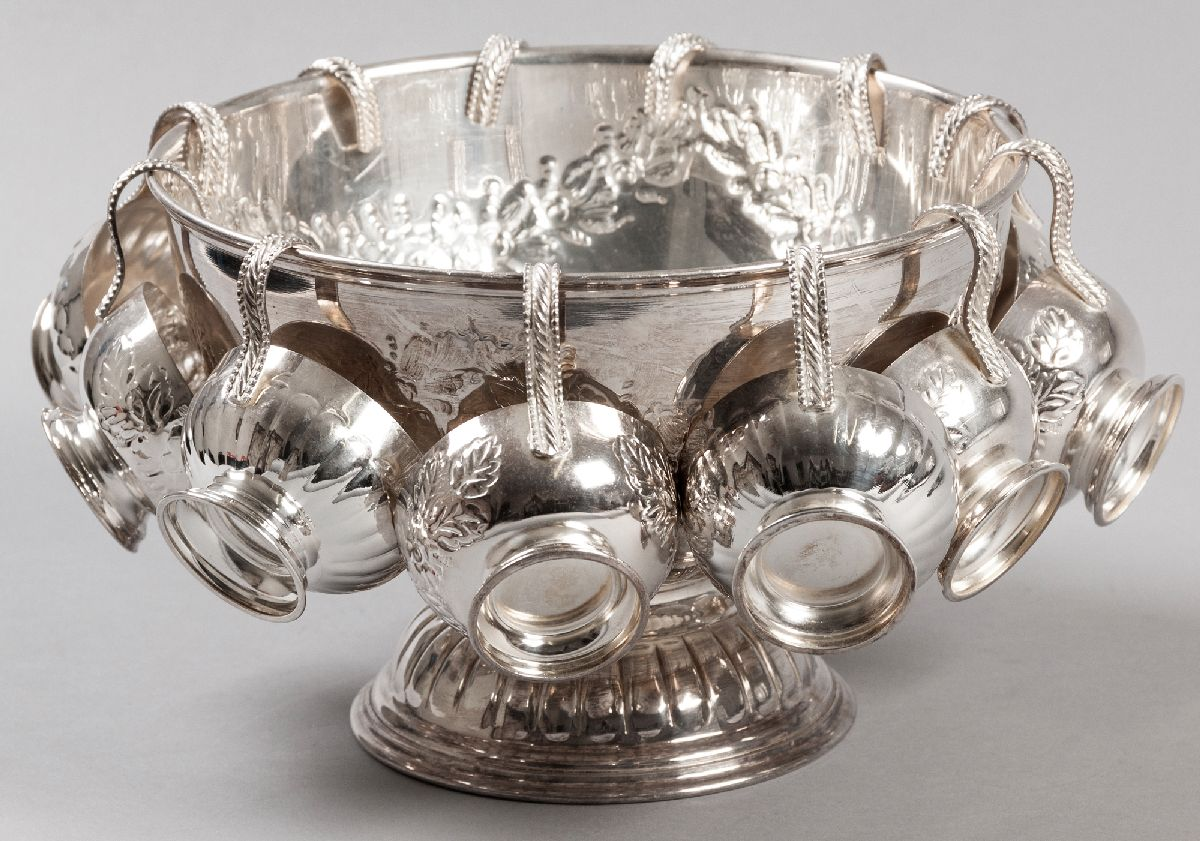 Lot 37 - A SILVERPLATE PUNCH BOWL WITH TWELVE CUPS, fold-over rim, the bowl emobssed with flowers and leaves,