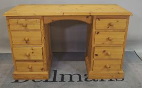 A modern pine pedestal desk comprising eight drawers about the knee, 122cm wide.