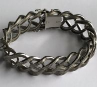 A 9ct white gold wide bracelet of abstract interlinked textured design,