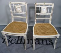 A pair of Regency style white painted side chairs on sabre supports, (2).