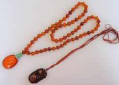 An Asian amber and jade pendant necklace, the front with an oval amber drop, with a jade surmount,