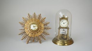 A brass aniversary clock housed under a glass dome,