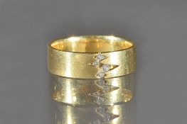 An 18ct gold and diamond set band ring, mounted with four circular cut diamonds in a zig-zag design,
