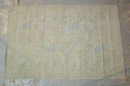 A machine made rug, ivory and blue, 178cm x 117cm.