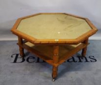 A mid-20th century birds eye maple octagonal coffee table with simulated bamboo border and inset