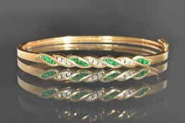 A gold, emerald and diamond set oval hinged bangle,