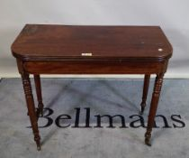 A late Victorian mahogany foldover tea table on ring turned tapering supports,
