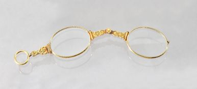 A pair of late Victorian 18ct gold framed lorgnettes, with floral and scroll engraved decoration,
