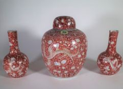 A late 19th/ early 20th century Asian red and white ginger jar decorated with dragons and a pair of