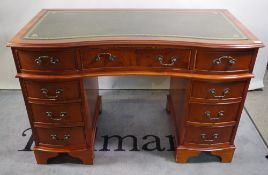 A 20th century yew wood veneered concave pedestal desk with green leather inset top,