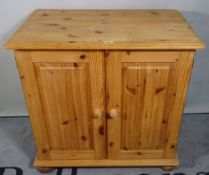 A 20th century pine side cupboard with a pair of panelled doors, 81cm wide x 72cm high.