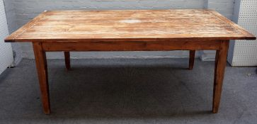 A stained pine kitchen table, the pegged biscuit joint plank top on tapering square supports,