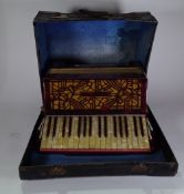An early 20th century cased leather piano accordion, 47cm wide x 41cm high.