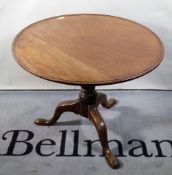 A George III style mahogany tripod table, with dished top on three outswept supports,