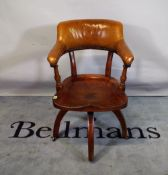 A late 19th century office armchair with elm slab seat and tan studded leather upholstery.