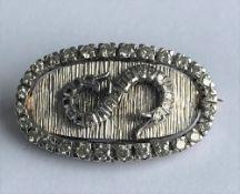 A white precious metal and diamond set brooch, of oval design, the central diamond set S motif,