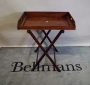 A late 19th century mahogany butlers tray with galleried top and folding stand,