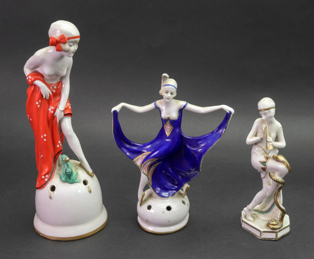 Lot 22 - A German porcelain figure, circa 1920's, modelled as a young lady snake charmer,