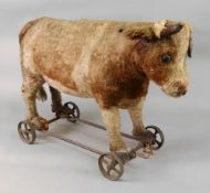 A blonde plush covered pull-along toy cow, late 19th century,