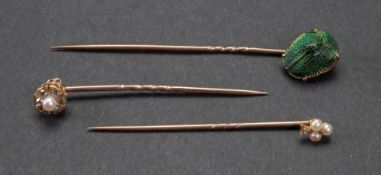 A collection of three rose precious metal stick pins,