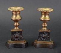 A pair of Empire gilt metal and bronze dwarf candlesticks,