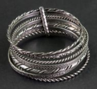 A semainier bangle, composed of a collection of seven silver bangles of varying designs,