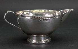 An Arts & Crafts silver milk jug, Birmingham 1920, makers mark T B, circular, spot hammered,