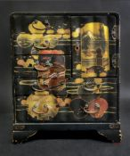 A Japanese black lacquered table top cabinet, Meiji, gilt and painted with landscape,