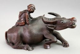 A Chinese carved hardwood figure of a child riding on the back of a water buffalo,